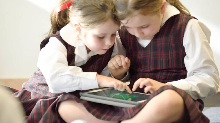 Two children studying at home with a tablet